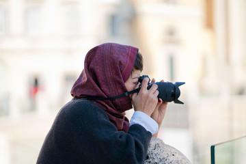 Femme avec un fourlard rouge sur la tête prenant une photo