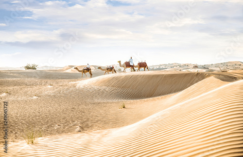 Man wearing traditional clothes, taking a camel out on the