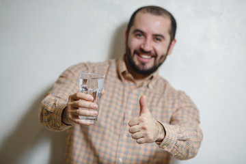Portrait of young man holding a glass of water and thumb up.