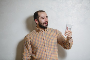 Young handsome man drinking a glass of water at home at a white background.