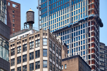 Water tank on an old building roof surrounded by modern skyscrapers in downtown New York, USA.