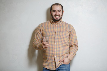 A young man holds a glass of water. On a white background.