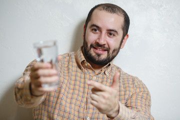 Portrait of young man holding a glass of water and pointing with his finger.