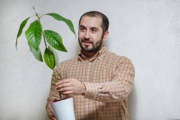 A smiling young man holding in hands an avocado tree flower. On a white background.