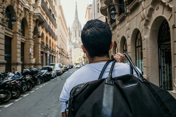 Traveler male looking on a big europe city, travel and active lifestyle concept.Bearded Tourist Man with black leather bag enjoy beautiful city travel