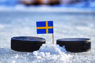 A Sweden flag on toothpick between two hockey pucks.  A Sweden will playing on World cup in group B. 2019 IIHF World Championship in Slovakia.