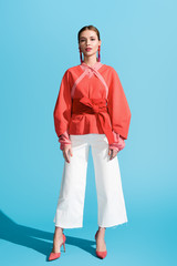 fashionable woman posing in living coral clothing on blue