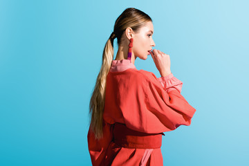beautiful stylish girl posing in trendy living coral clothing isolated on blue