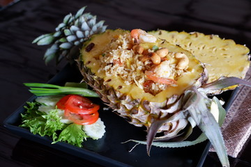 Fried rice with pineapple on wooden table