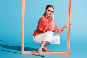 stylish model in living coral clothing and sunglasses posing with big frame on blue Wall mural