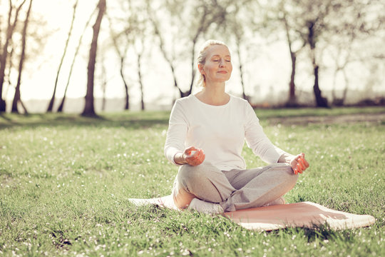 Relaxed mature woman doing yoga in park