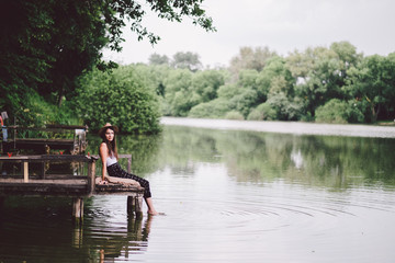 Relaxing woman at a summer lake in forest
