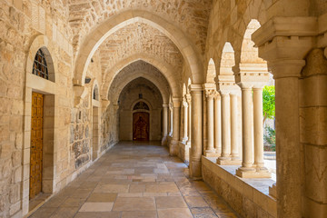 The inner courtyard of the Church of the Nativity is surrounded by beautiful covered terraces with stone columns, Bethlehem, Palestine.