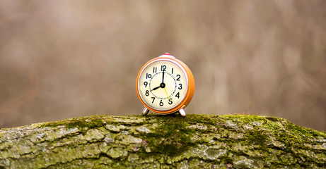 Daylight savings time - web banner of an alarm clock as standing on a wood