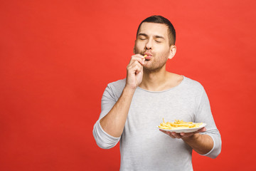 Young man holding french fries. Student eats fast food. Not helpful food. Very hungry guy. Diet concept. Isolated over red background.
