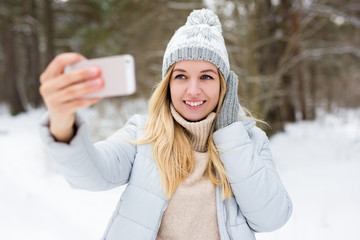 portrait of young blond woman taking selfie photo in winter park or forest