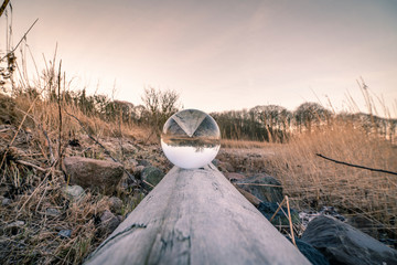 Crystal ball in balance on a wooden log