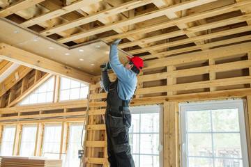 Construction worker thermally insulating eco wooden frame house