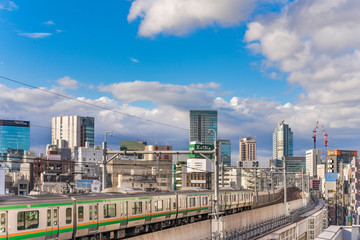 kanda station where the trains of the yamanote line pass between the top of the buildings of the district of Chiyoda under the blue sky of Tokyo.