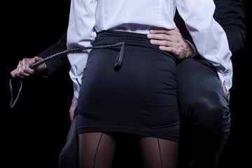 Man hand holding whip on woman ass in mini skirt