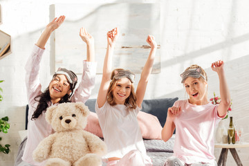 beautiful smiling multicultural girls looking at camera and stretching in  morning during pajama party 2a9656484