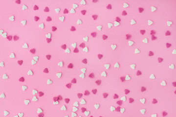 Candy sweets sugar sprinkle decoration in shape of heart on a pink background for wallpaper, card, invitation or poster