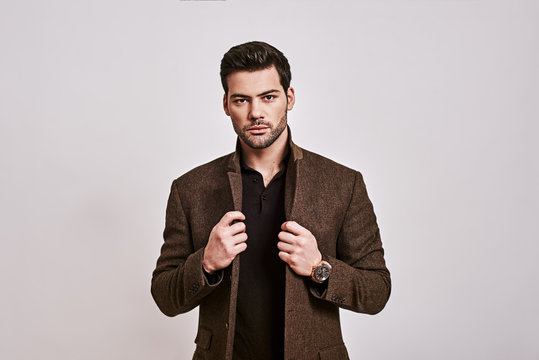 Looking just perfect. Stylish dark-haired man holding his jacket and looking at camera isolated over grey background