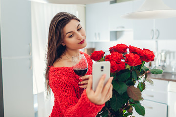Young woman found bouquet of roses on kitchen. Happy girl taking selfie on phone drinking wine. Valentines day