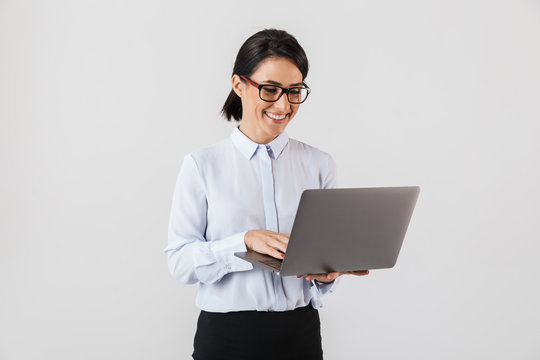 Portrait of businesslike woman wearing eyeglasses holding silver laptop in the office, isolated over white background