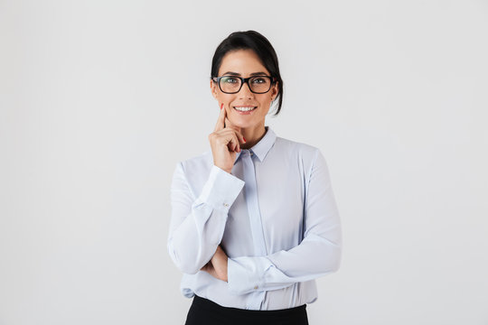 Photo of successful businesswoman wearing eyeglasses standing in the office, isolated over white background