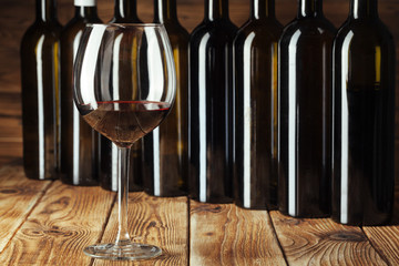 Wine bottles with glass, wooden background