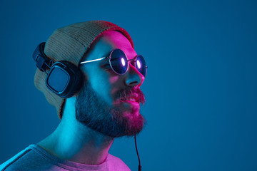 Photo sur Plexiglas Magasin de musique Enjoying his favorite music. Happy young stylish man in hat and sunglasses with headphones listening and smiling while standing against blue neon background