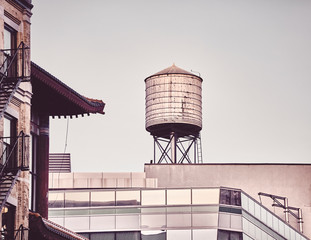 Retro toned picture of a rooftop water tower in downtown New York, USA.
