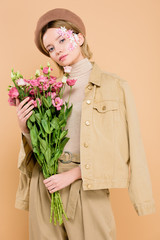 trendy woman with flowers on face holding bouquet isolated on beige