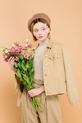 stylish woman with flowers on face holding bouquet isolated on beige