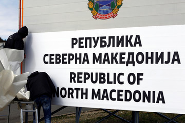 Workers set up a sign with Macedonia's new name at the border between Macedonia and Greece, near Gevgelija