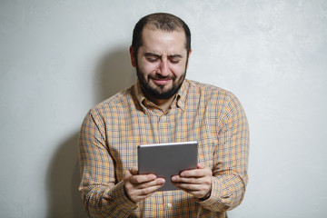 Happy man with a modern smartphone in his hands, playing in games. The man with a smile and beauty shows different emotions on a white background.