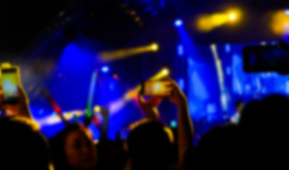Blurred people are taking photo concert with smartphones, fun concert.