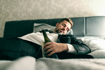 Drunk businessman in suit lying in the bed and sleeping with bottle of alcohol in his hand. Alcohol abuse concept.