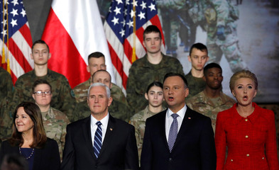 U.S. Vice President Mike Pence, his wife Karen, Polish President Andrzej Duda and his wife Agata Kornhauser-Duda attend Pence's arrival at the airport in Warsaw
