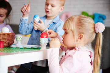 Close up of focused girl decorating easter egg