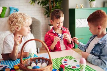 Three happy boys painting easter eggs