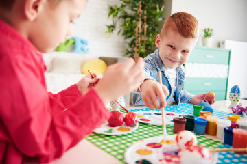 Smiling boy painting easter eggs