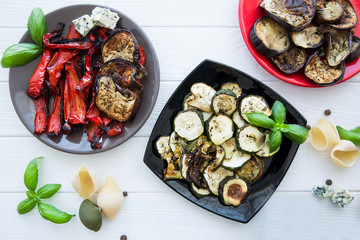 Grilled vegetables on white wooden table, grilled paprika, zucchini and eggplants. Conchiglie and fresh basil decorations, blue cheese and allspice.