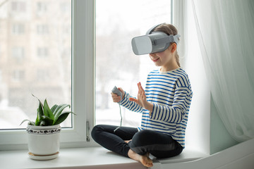A child with a virtual reality headset is sitting at the table indoors at home. A girl exploring the world of virtual reality through video and games.