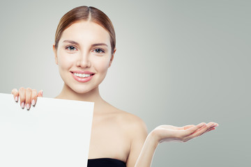 Healthy woman laughing, showing empty open hand and white paper banner board background