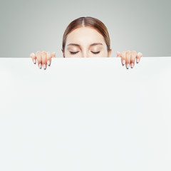 Young woman looking down and showing white empty paper card background with copy space for advertising marketing or product placement