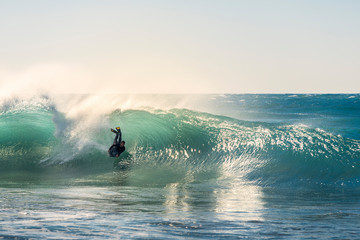 Surfer glides by a wave in the light of sunset