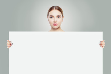 Healthy woman and big white empty paper board background in her hands