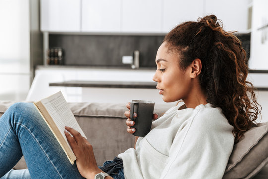 Image of adorable african american girl reading book and drinking tea, while sitting on sofa in bright flat